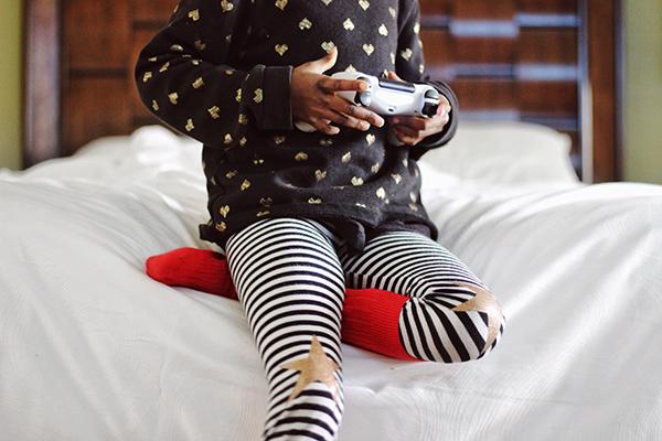 Lapsi pelaa peliohjain kädessä