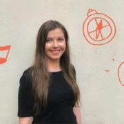 Hymyilevä nainen, ruskeat hiukset ja musta paita, ympärillä piirrettyä kuvituskuvaa kuten sydän, kynä ja yksisarvinen. Mediakasvatusseuran logo.
