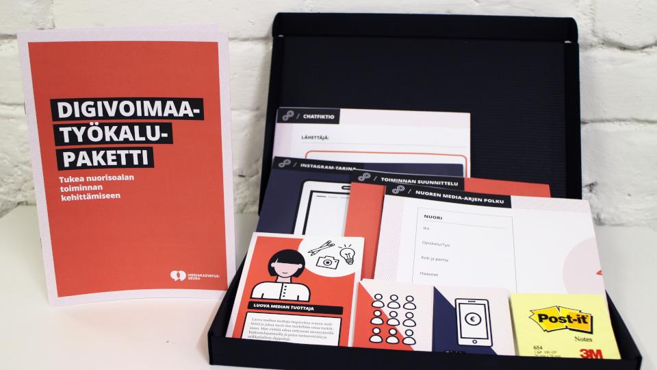 Kuvassa konkreettisen työkalupaketin materiaalit: Tehtäväkirja, kanvaita, kortteja ja post it -lappuja.