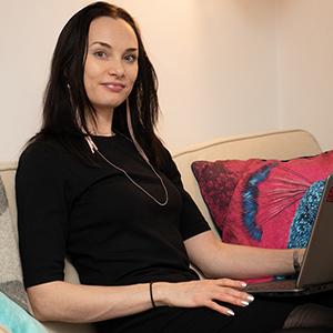 valokuva Marjosta; hymyilevä tummatukkainen Marjo istuu läppäri sylissä sohvalla